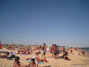 Tourists enjoy the beach in Portugal while we work indoors